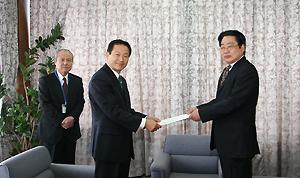 中野委員長が市長に報告書を手渡している様子