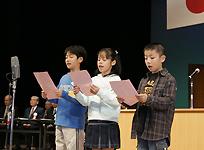 式典で市民憲章を読み上げる小学生3人