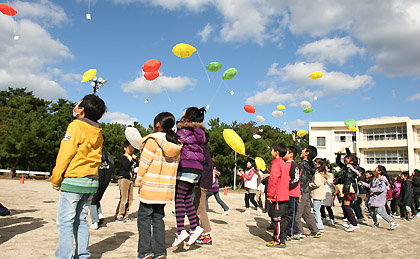飛んでいくエコ風船に歓声をあげる西小学校の生徒