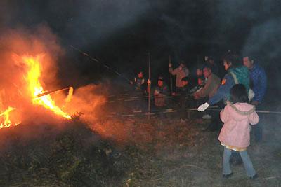 竹の棒に餅をつけて火にかざしている様子