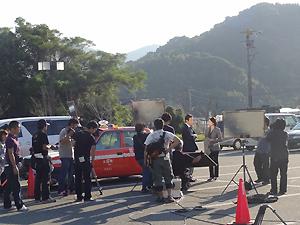 タクシー右横に立つ、渡瀬恒彦さんと宮本真希さん