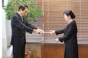 松本由美子さんに辞令を渡す市長